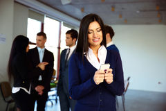 Businesswoman using smartphone with colleagues Royalty Free Stock Images