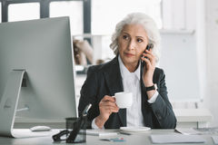 Businesswoman using smartphone and drinking coffee at workplace in office Royalty Free Stock Photography
