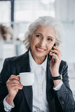 Businesswoman using smartphone and drinking coffee at workplace in office Stock Images