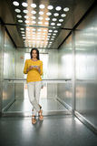 Businesswoman using smartphone in elevator Royalty Free Stock Photo