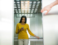 Businesswoman using smartphone in elevator Stock Images