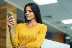 Businesswoman using smartphone in office Royalty Free Stock Image