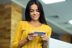 Businesswoman using smartphone in office Stock Photo