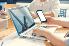 Businesswoman using smartphone while working in office. Soft focus, vintage tone Royalty Free Stock Photography