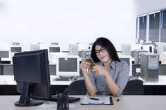 Businesswoman using a smartphone in the workplace Royalty Free Stock Photos