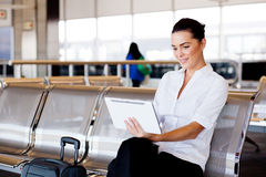 Businesswoman using tablet at airport. Young attractive businesswoman using tablet computer at airport Royalty Free Stock Images