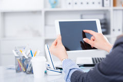 Businesswoman using tablet. Business woman holding and using tablet at workplace in office Stock Photography