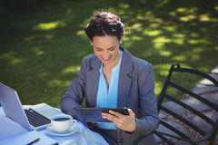 Businesswoman using tablet with coffee Stock Images