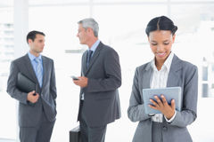 Businesswoman using a tablet with colleagues behind Royalty Free Stock Photo