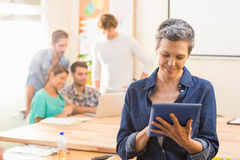 Businesswoman using a tablet with colleagues behind Stock Image