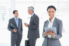 Businesswoman using a tablet with colleagues behind in office Royalty Free Stock Images