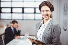 Businesswoman using tablet computer while colleague in background Royalty Free Stock Photo