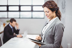 Businesswoman using tablet computer while colleague in background Stock Photography