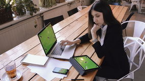 Businesswoman using tablet computer with green touch screen in cafe on wood table. Young beautiful student reads a tablet and work on laptop pc with cell phone stock footage