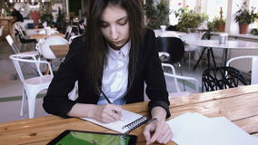 Businesswoman using tablet computer with green touch screen in cafe. Young beautiful student reads a tablet and make notepads in a notepad sitting in a loft stock video footage