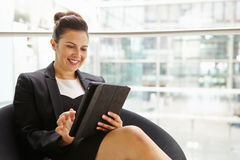 Businesswoman using tablet computer in modern interior Stock Image