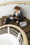 Businesswoman Using Tablet Computer Sitting On Stairs Royalty Free Stock Photo