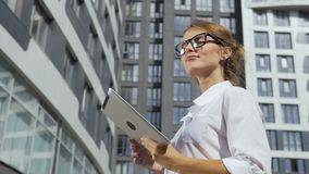 Businesswoman using tablet in front of corporation. Smiling and self-confident young dark hair caucasian businesswoman, in a white blouse and stylish glasses, is stock video footage