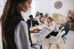 Businesswoman using tablet with instagram app on screen at office with blurred overworked coleagues sitting. At conference room royalty free stock image