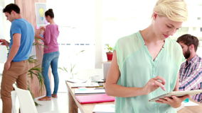 Businesswoman using tablet in the office with colleagues behind. In the office stock video footage