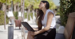 Businesswoman using a tablet in an urban park. Attractive stylish young businesswoman using a tablet in an urban park as she sits relaxing on a bench  profile stock video