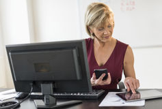 Businesswoman Using Technologies At Computer Desk. Mature businesswoman using technologies at computer desk in office Royalty Free Stock Photo
