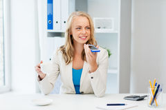 Businesswoman using voice command on smartphone. Business, tecnology, communication and people concept - happy businesswoman drinking coffee and using voice Royalty Free Stock Images