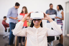 Businesswoman using vr glasses. With colleagues in background Royalty Free Stock Images