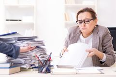 The businesswoman very busy with ongoing paperwork. Businesswoman very busy with ongoing paperwork Royalty Free Stock Images