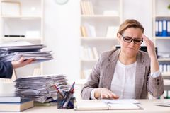 The businesswoman very busy with ongoing paperwork. Businesswoman very busy with ongoing paperwork Royalty Free Stock Photography