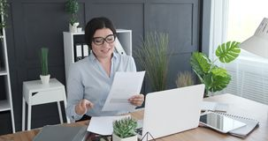 Businesswoman video conferencing using laptop at office. Young businesswoman holding documents doing video conference using laptop at office stock video footage
