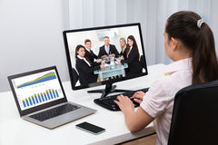 Businesswoman Videoconferencing On Computers Stock Image