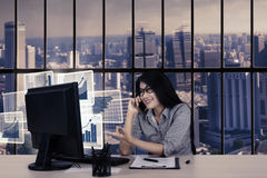 Businesswoman with virtual growth graphs and phone Royalty Free Stock Images