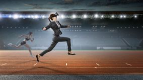 Feel virtual reality. Mixed media. Businesswoman in virtual mask running at stadium. Mixed media stock photography