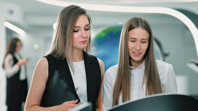 Businesswoman at virtual reality development center or exhibition. Medium shot two young female scientific developer discussing hi-tech application modern