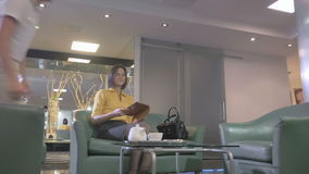 Businesswoman wait the order in hall of the hotel. Beautiful girl in yellow shirt sitting on the green sofa in the hall of the hotel. She`s using tablet. The stock video footage