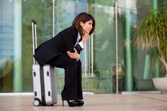 Businesswoman waiting at an airport. Cute young businesswoman waiting for her next flight at an airport and sitting on her suitcase Royalty Free Stock Image