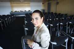 Businesswoman waiting in empty lecture hall Royalty Free Stock Photos