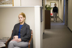 Businesswoman waiting in office lobby. Young woman waiting in office lobby holding coffee cup Stock Photography