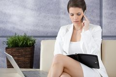 Businesswoman waiting in office lobby, working Royalty Free Stock Image
