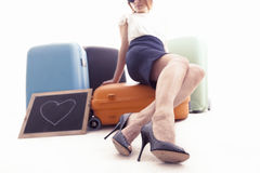 Businesswoman waiting sitting over her suitcases Royalty Free Stock Photos