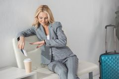 Businesswoman waiting for trip. Businesswoman looking at watch while waiting for trip Stock Images