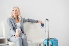 Businesswoman waiting for trip. Thoughtful businesswoman with coffee to go waiting for trip Stock Photo