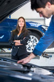 Businesswoman waits for a mechanic to fix her car Stock Images