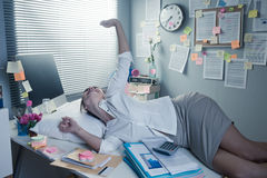 Businesswoman waking up on office desk Stock Photo