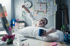 Businesswoman waking up in office Stock Photo