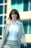 Businesswoman Walk 4 Blue Tint. Serious businesswoman walking outside of an office building.  Blue tinted Stock Image