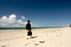 BusinessWoman Walking. At the beach carrying balck suitcase Stock Photo