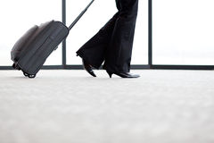 Businesswoman walking in airport. With her luggage Royalty Free Stock Images