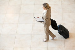 Businesswoman walking airport. Young businesswoman walking at airport with luggage Stock Photos